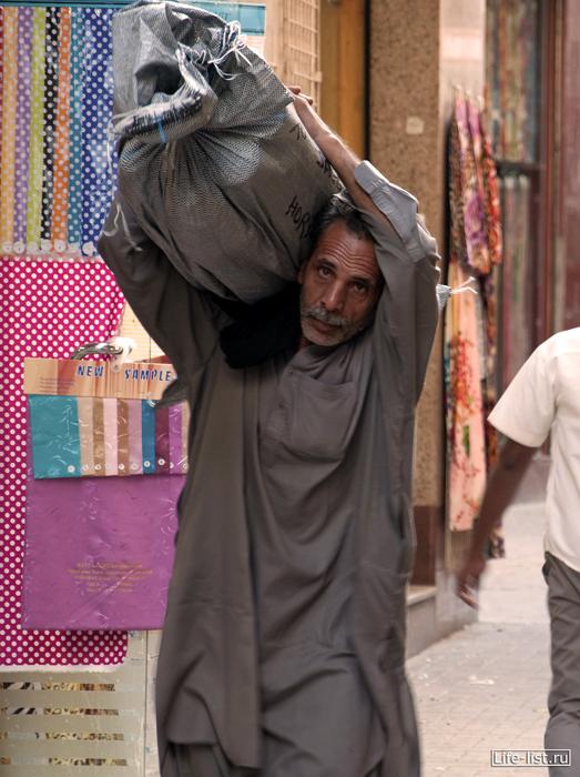 мужчина несет мешок в дубае рынок