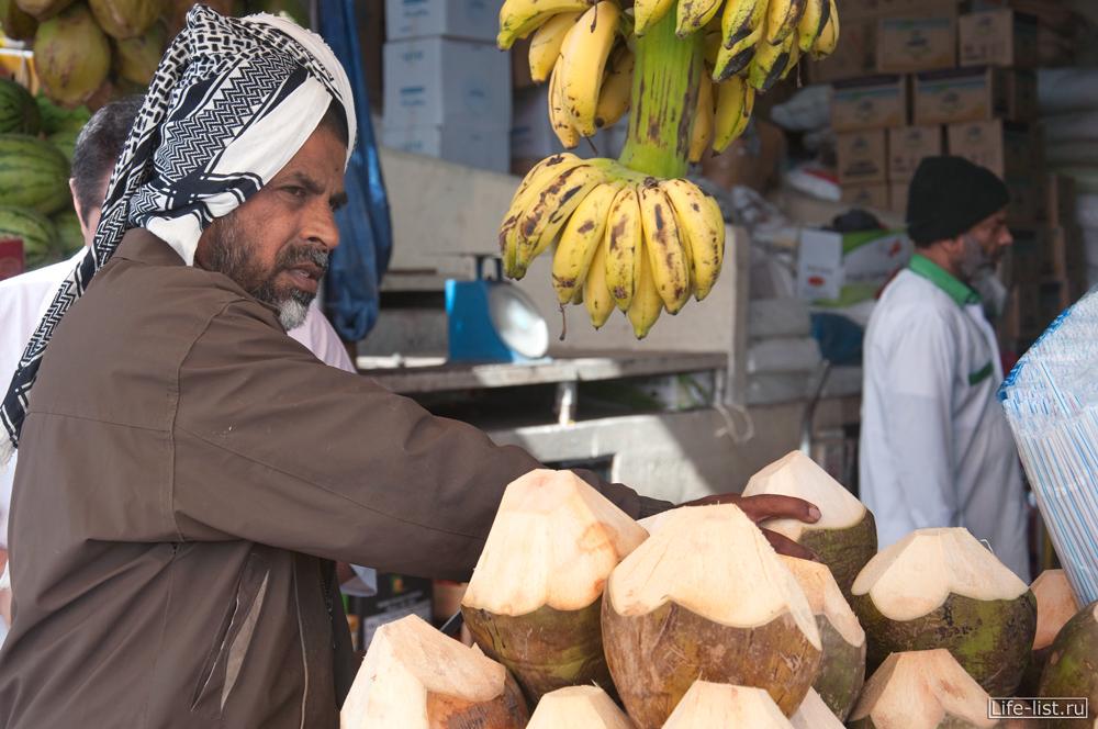 продавец кокосов на овощном рынке в дубае