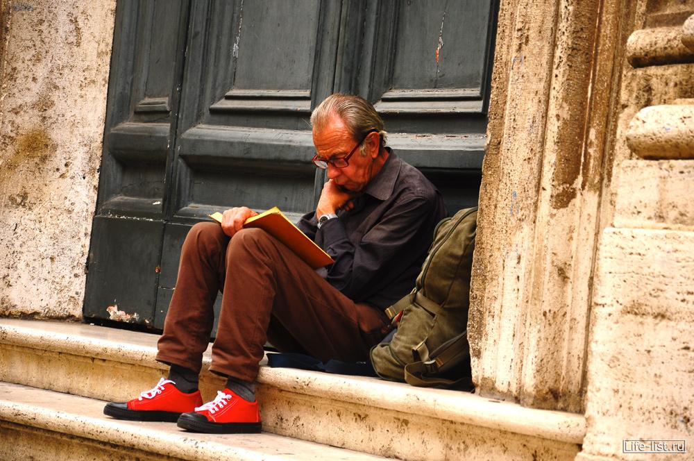 Мужчина путник читает книгу в красных кедах фото foto by Karavan