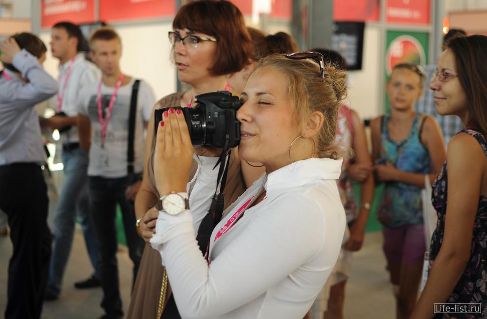девушка с фотоаппаратом на выставке иннопром в екатеринбурге