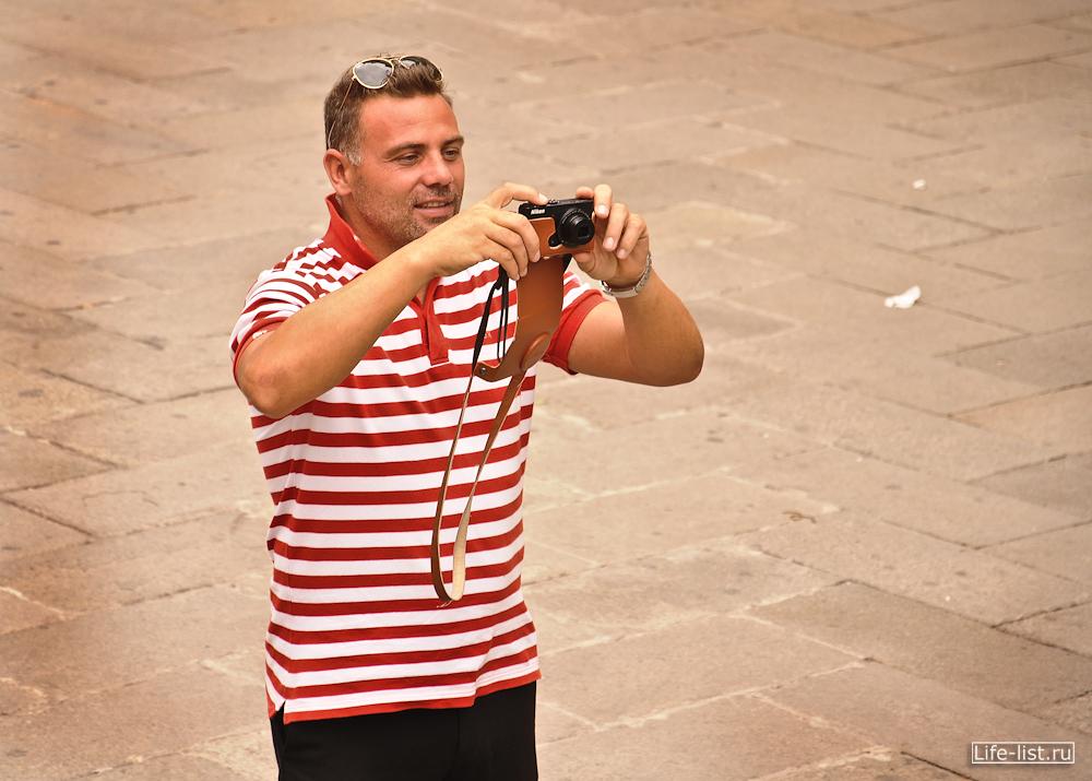 Гондольер фотографирует туристов