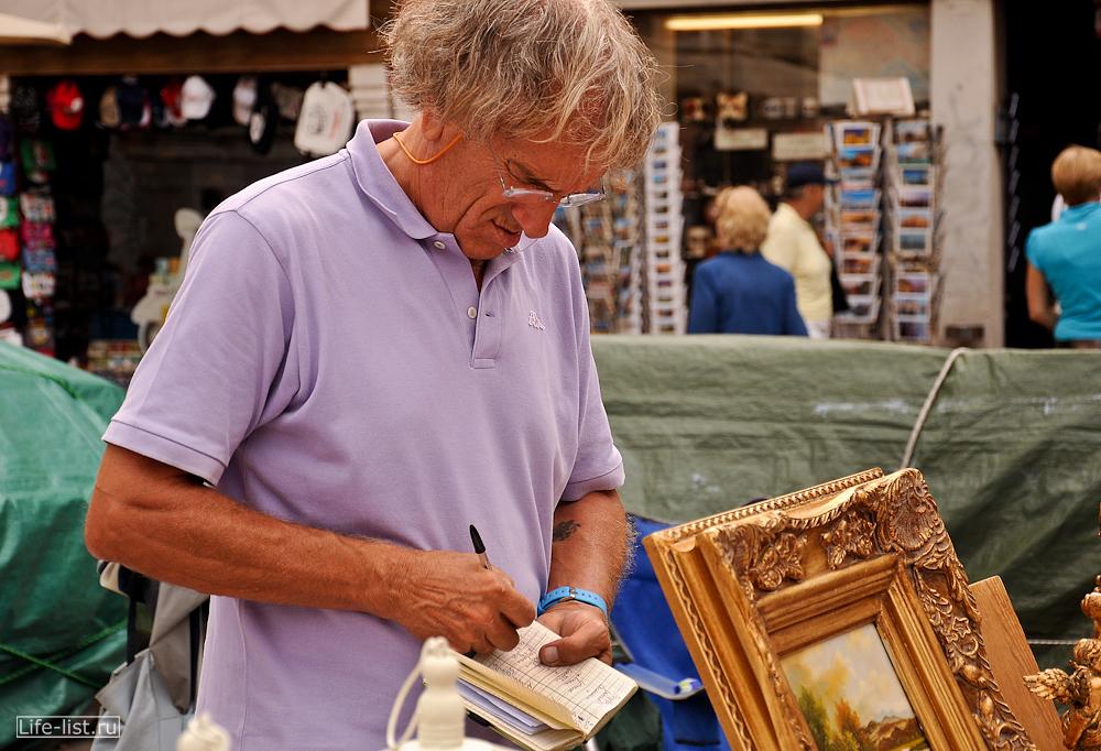 Продавец на блошином рынке в Венеции
