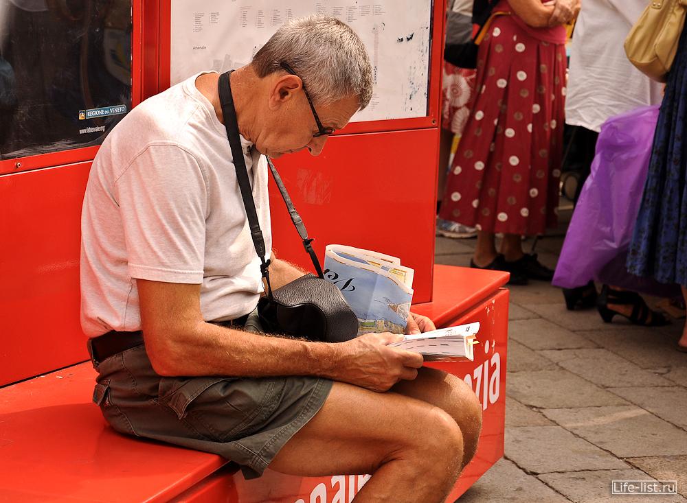 Турист читает путеводитель по Венеции