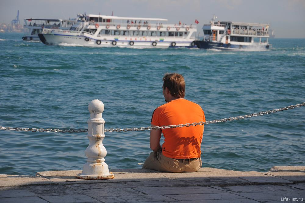 на берегу Босфора сидит мужчина