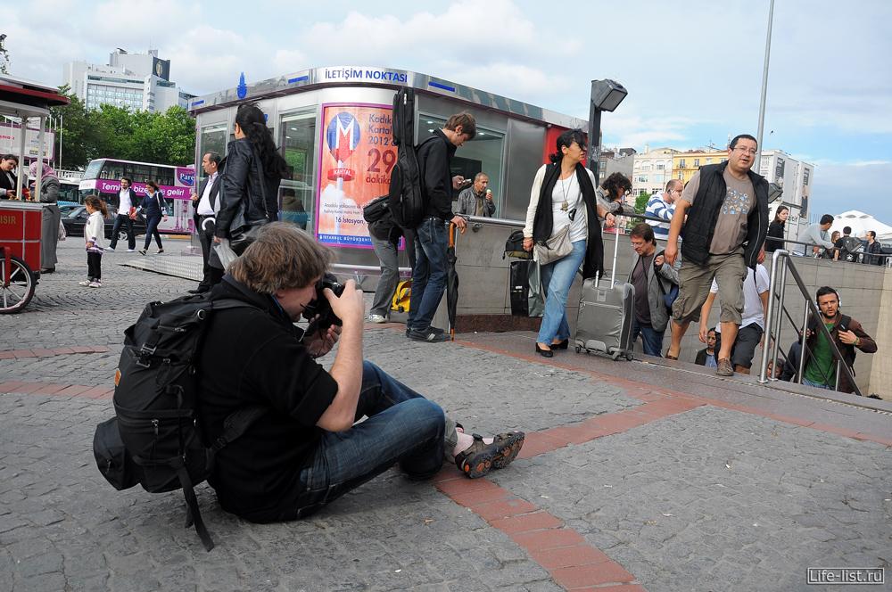 фотограф сидит на асфальте и делает стрит жанр