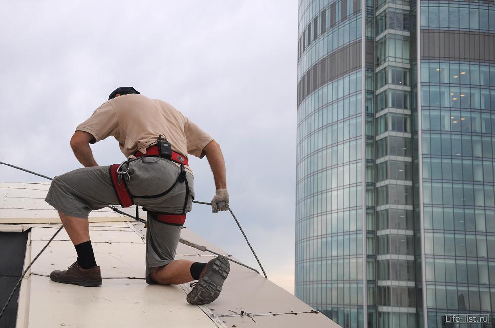 промышленный альпинист готовится завешаться БЦ Антей