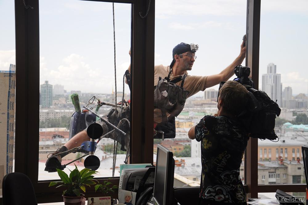 высотный клининг за окном офиса моет окна на высоте