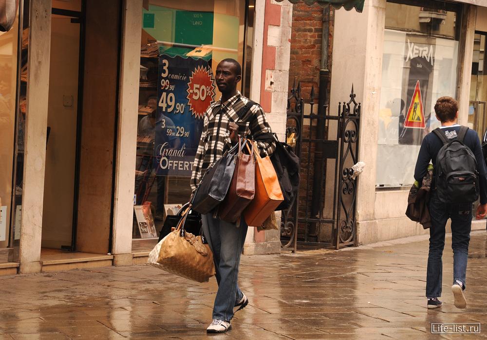 Темнокожие на улице Венеции продают сумки Италия торговля