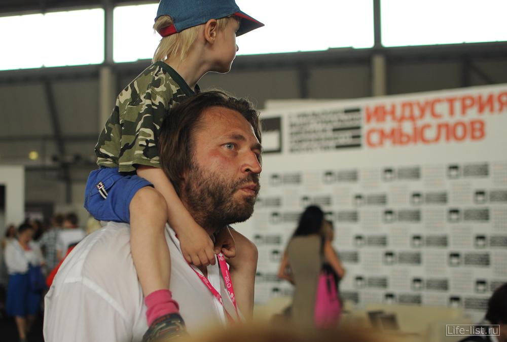 Мужчина с ребенком на шее посетитель выставки иннопром