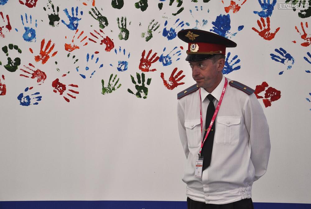 стена с отпечатками ладоней на выставке иннопром и полицейский