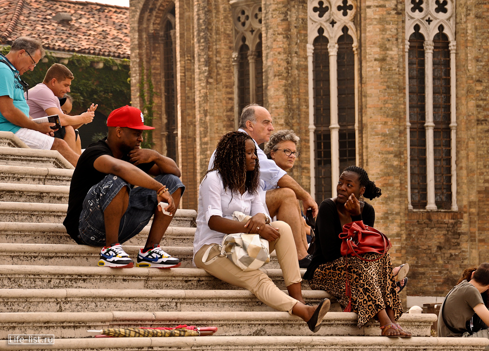 туристы отдыхают на ступеньках собора Санта Мария в Венеции