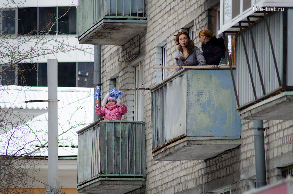 люди на балконе смотрят эстафету олимпийского огня факел Екатеринбург