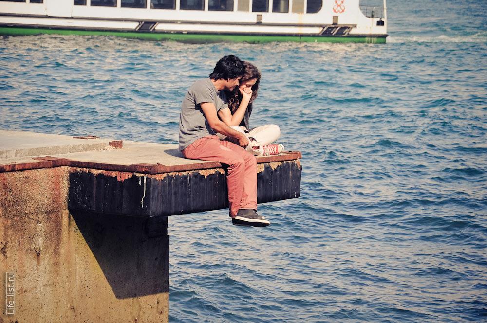 молодые люди сидят на берегу Босфора