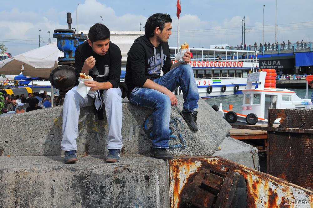 Парни едят на улице в стамбуле